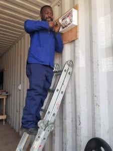 Motebang working on the power supply in the site office container